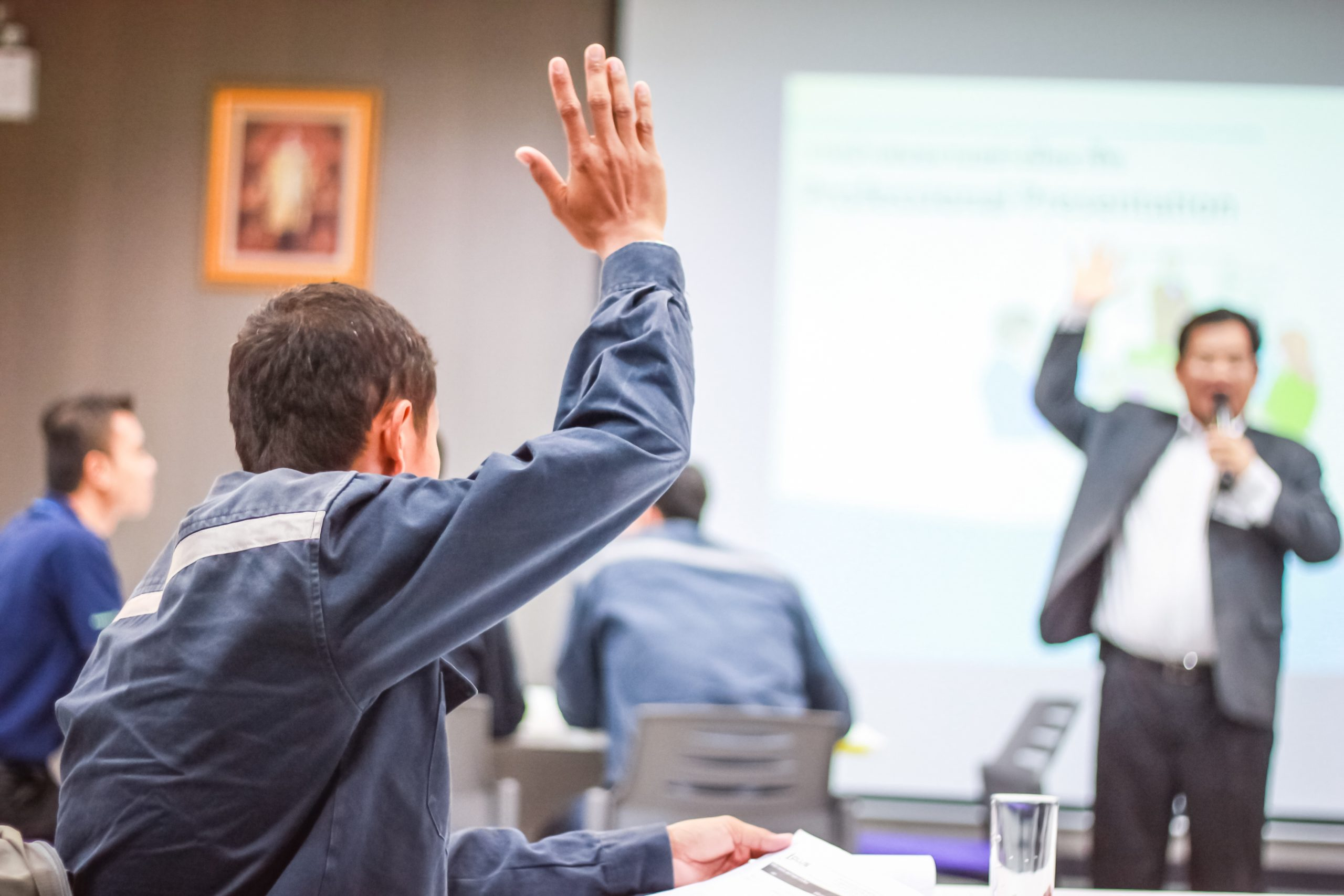 Student with raised hand in classroom