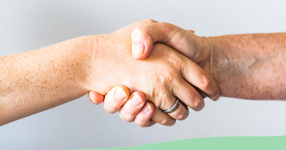 Image: Hands of two people clasped together in cooperation