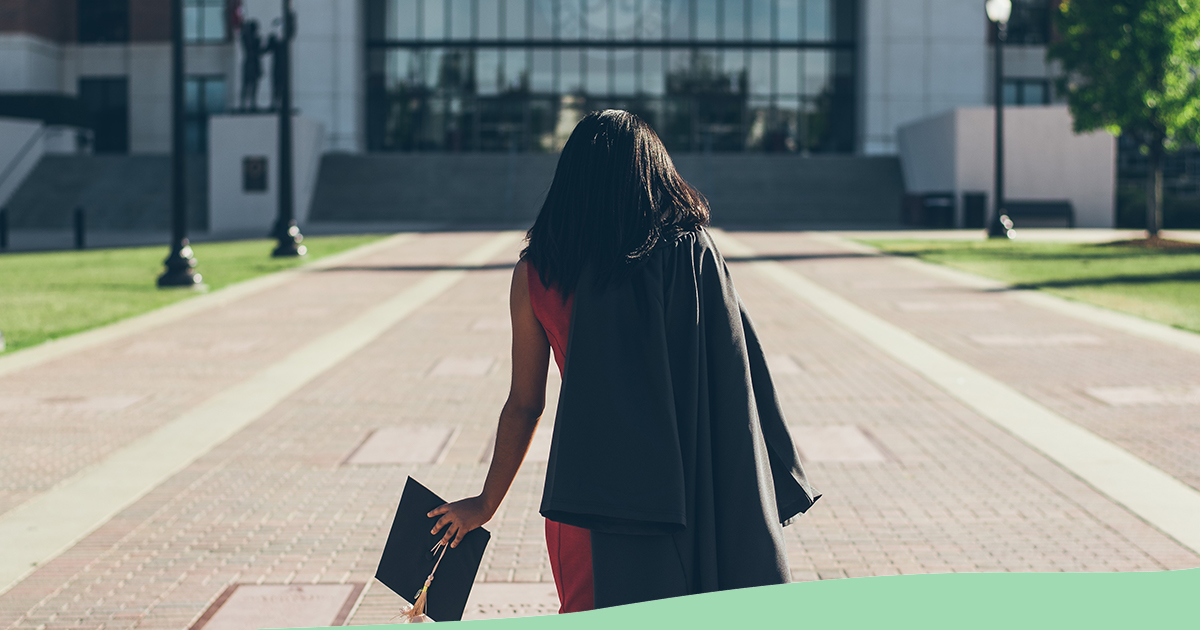 Image: Woman walks towards a campus building with a graduation cap in hand
